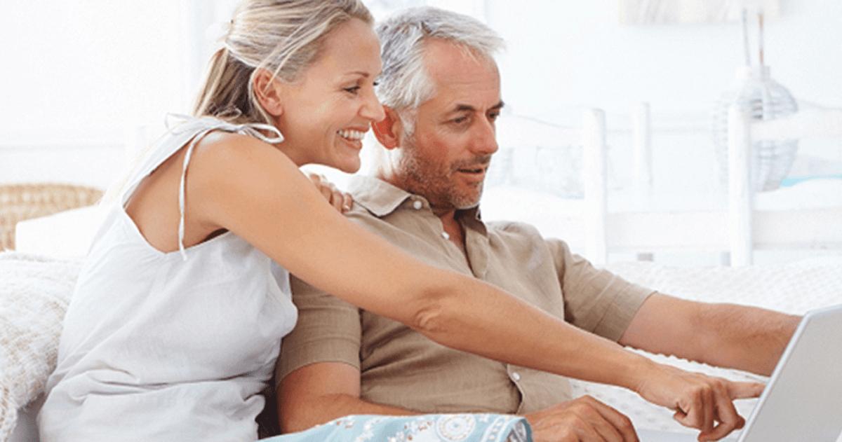 Man en vrouw zitten op de bank met laptop op schoot